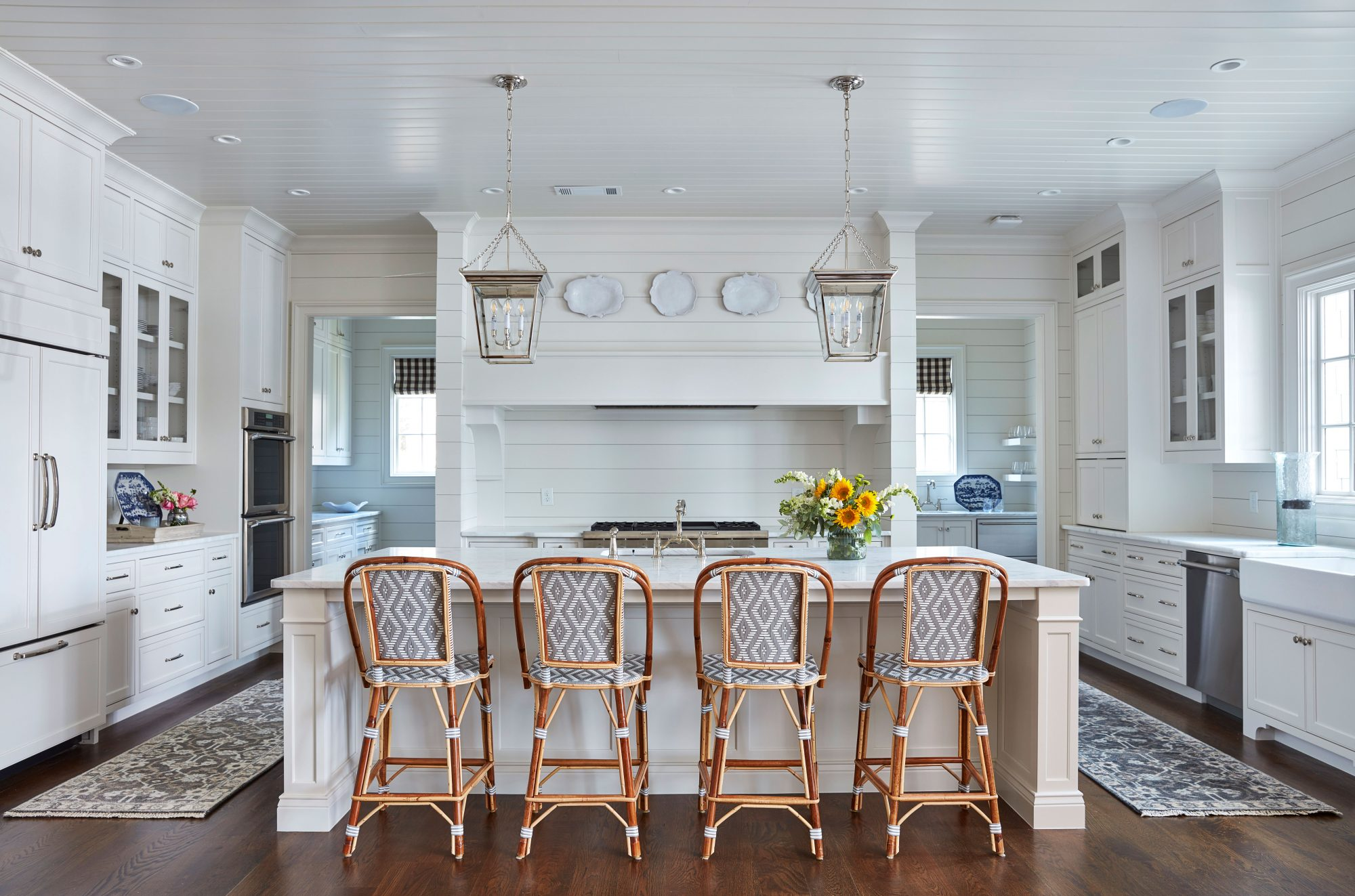 White Kitchen with Large Island and Rattan Barstools