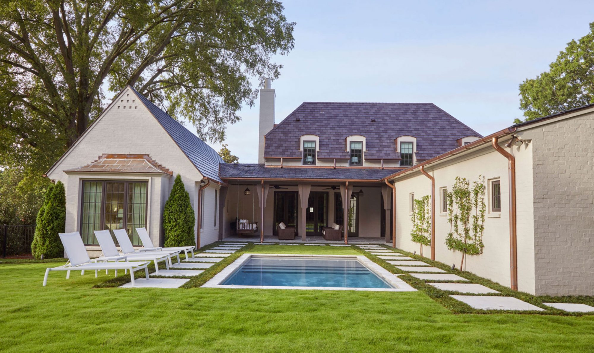 Rectangular Pool Behind House with Grass and Stepping Stones