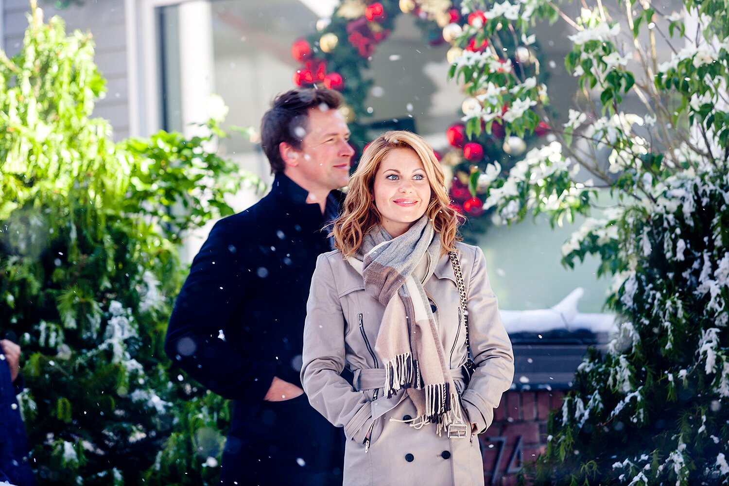candace cameron next to a man in a black coat in the snow