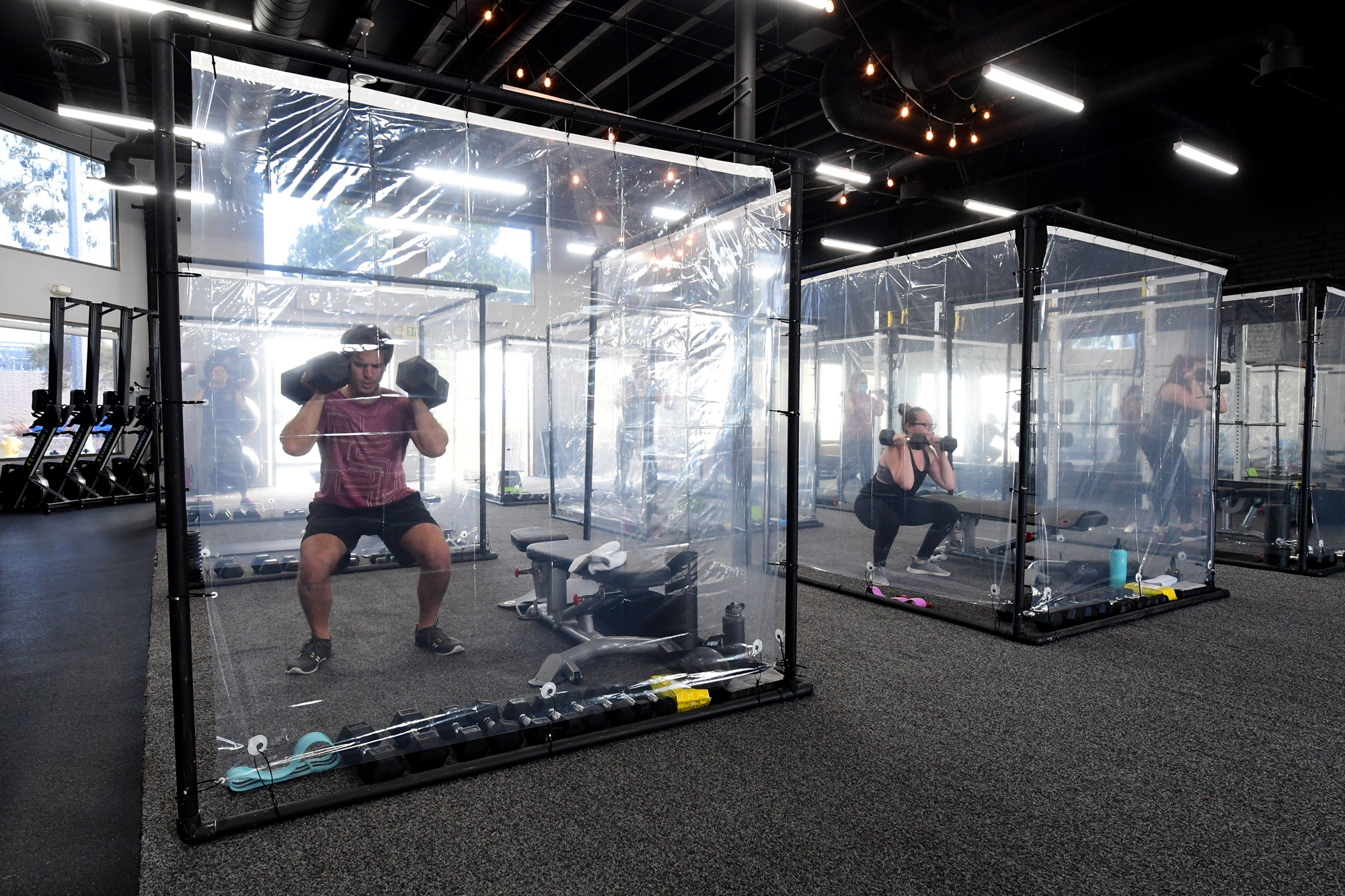 People exercise at Inspire South Bay Fitness behind plastic sheets