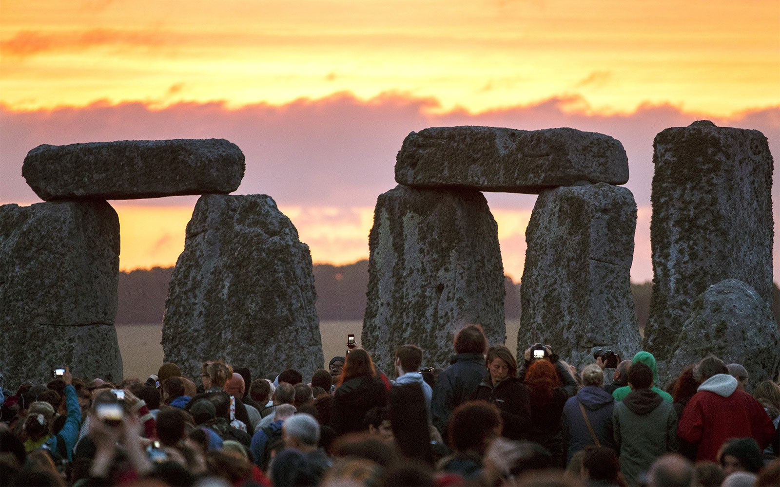 SALISBURY, UNITED KINGDOM - JUNE 21: People take photos of the Summer Solstice sunrise at Stonehenge on June 21, 2015 in Wiltshire, England. Thousands of revellers gather at the 5,000 year old stone circle in Wiltshire to see the sunrise on the Summer Solstice dawn. The solstice sunrise marks the longest day of the year in the Northern Hemisphere. (Photo by Tolga Akmen/Anadolu Agency/Getty Images)