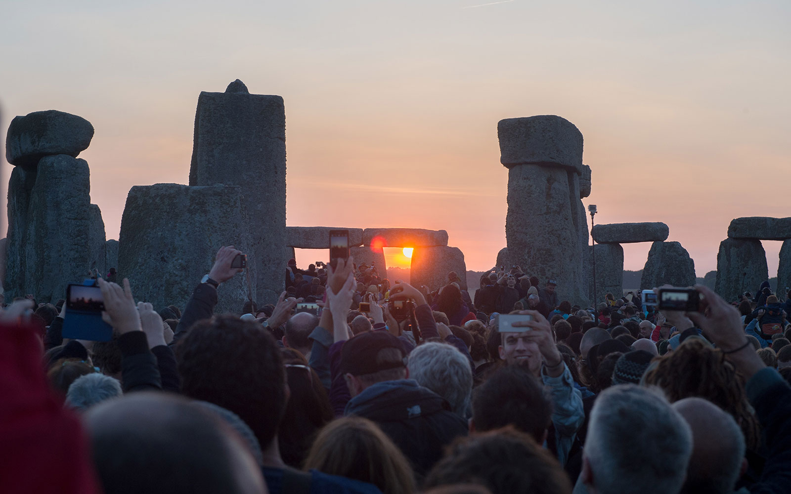 WILTSHIRE, ENGLAND - JUNE 21:  People take part in the summer solstice dawn celebrations after druids, pagans and revellers gathered for the Summer Solstice sunrise at Stonehenge on June 21, 2014 in Wiltshire, England. A sunny forecast brought thousands of revellers to the 5,000 year old stone circle in Wiltshire to see the sunrise on the Summer Solstice dawn. The solstice sunrise marks the longest day of the year in the Northern Hemisphere.  (Photo by Tim Ireland/Getty Images)