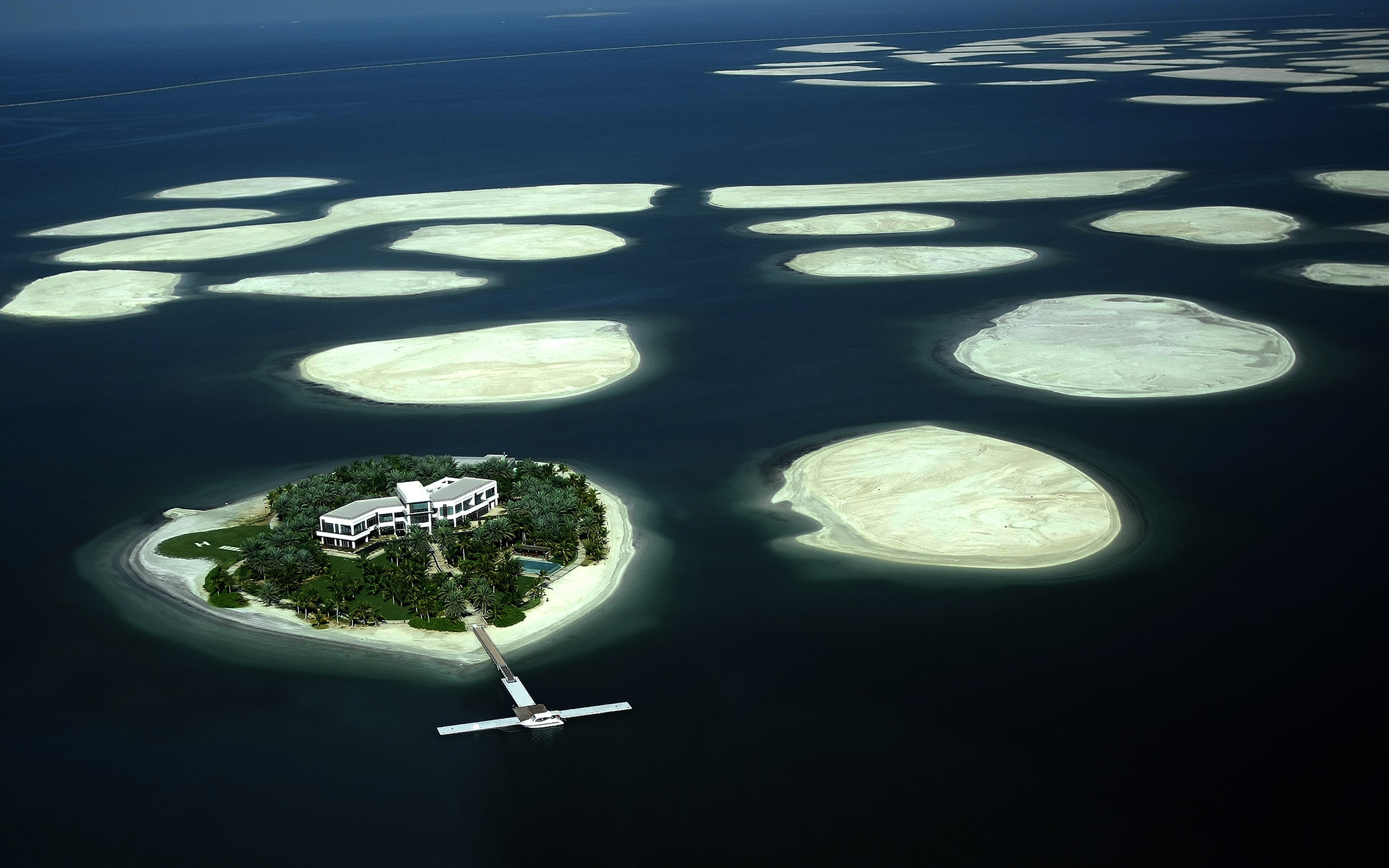"(FILES) A picture taken on December 21, 2009 shows an aerial view of a cluster of man-made islands known as ""The World"" by Emirati property developers Nakheel off the coast of Dubai. The real state project is stable, its developer Nakheel insists, despite"