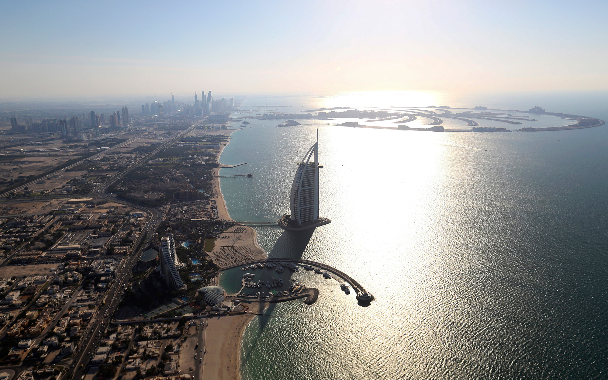 City skyscrapers stand on the skyline beyond the Burj Al Arab luxury hotel, center, Jumeirah Beach hotel, center left, and the Jumeirah Palm archipelago, top right, on the shoreline of Dubai, United Arab Emirates, on Tuesday, Nov. 11, 2014. Declining curr
