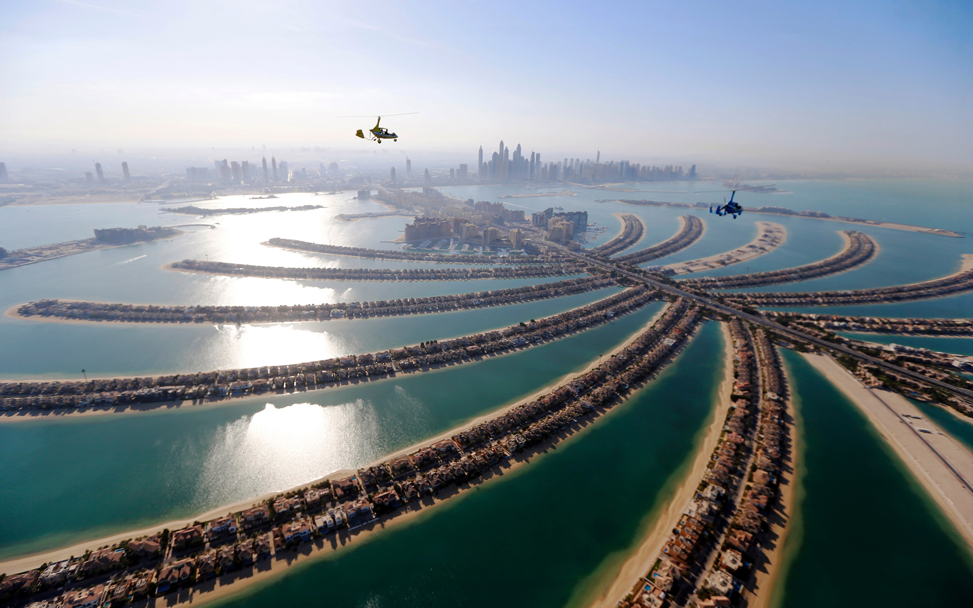 TOPSHOT - Gyrocopters fly over the capital of the United Arab Emirates, Dubai, during the World Air Games 2015, on December 9, 2015. AFP PHOTO / KARIM SAHIB / AFP / KARIM SAHIB        (Photo credit should read KARIM SAHIB/AFP/Getty Images)