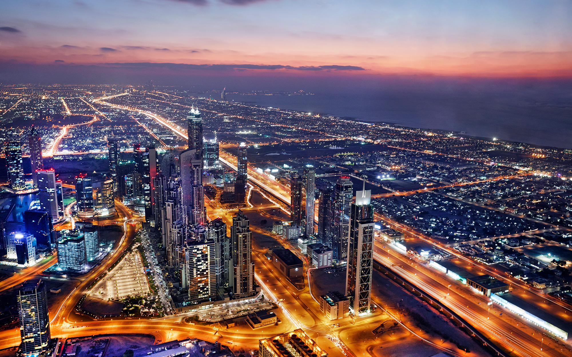 Elevated cityscape of Dubai illuminated at dusk