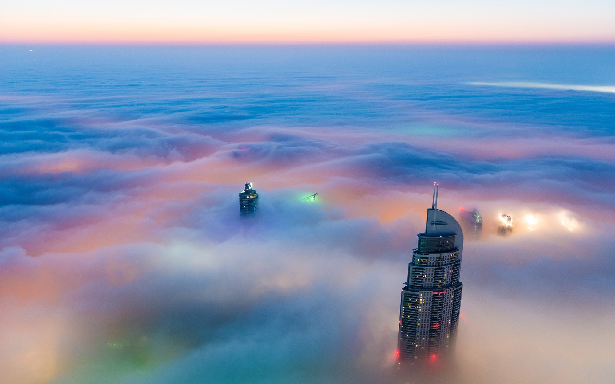 Overlooking Downtown Dubai during sunrise with lights shining through the blanket of white fog. Dubai, United Arab Emirates
