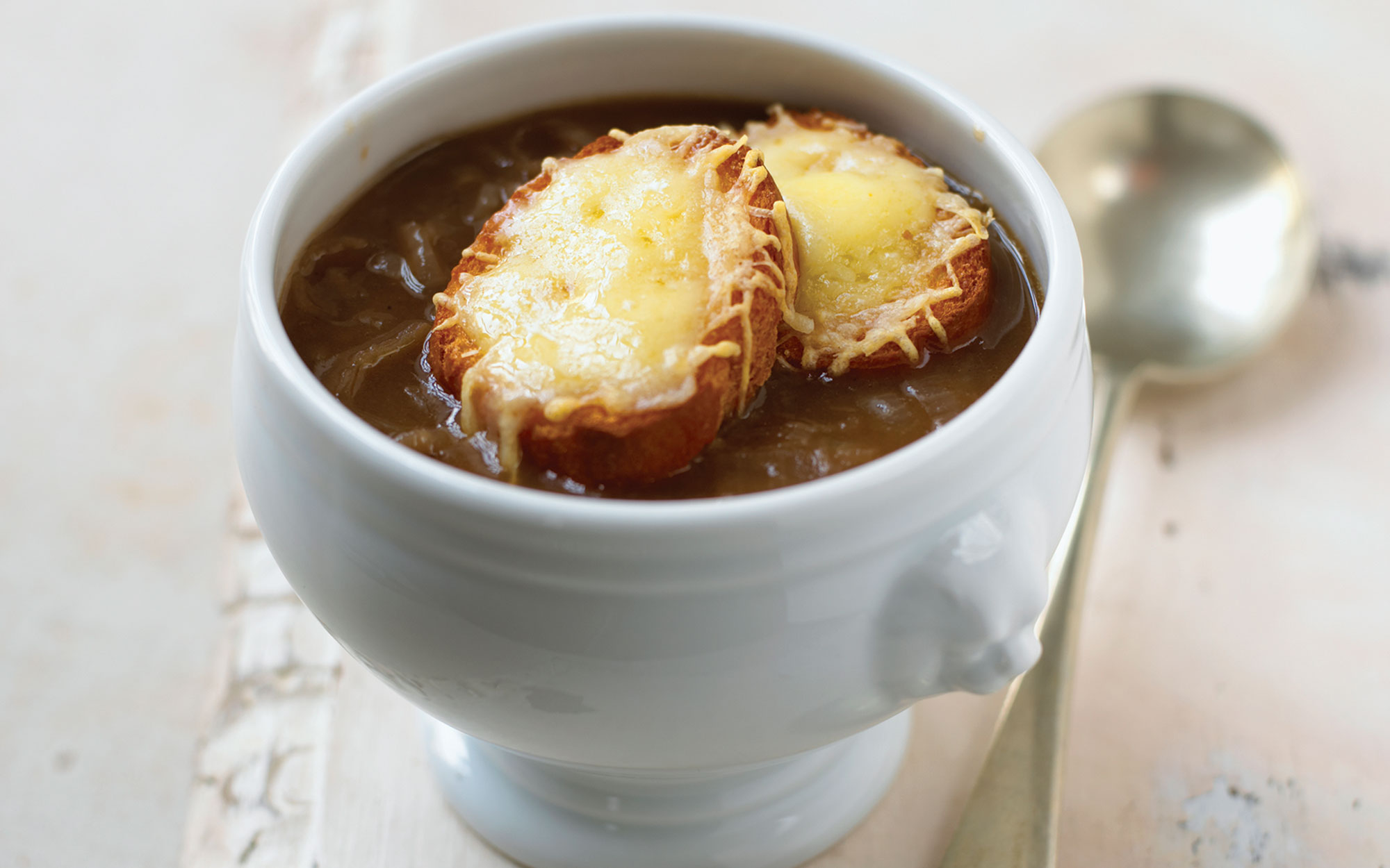 French onion soup served in bowl topped with toasted bread and melted grated cheese, close-up