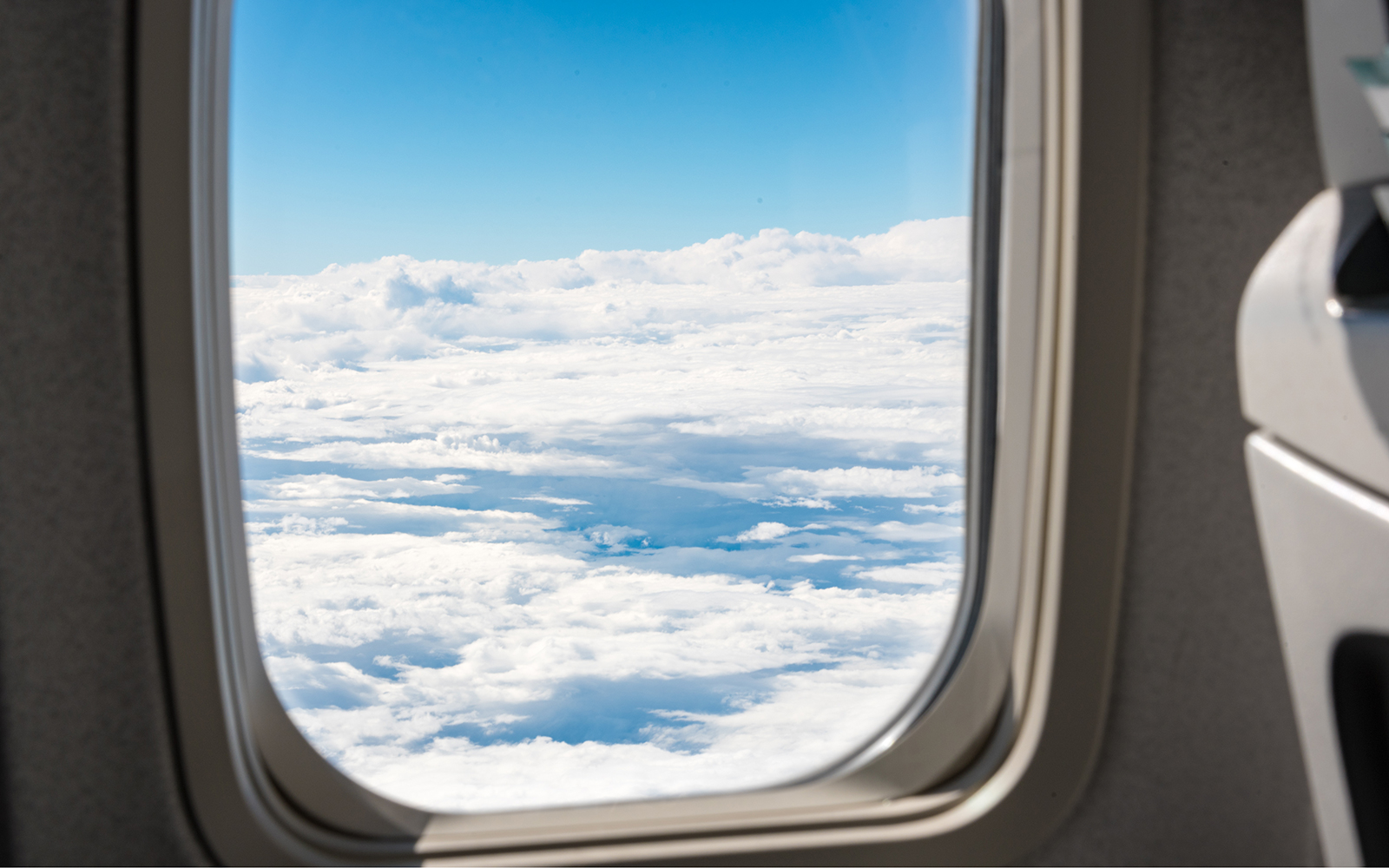 Airplane window with clouds and blue sky