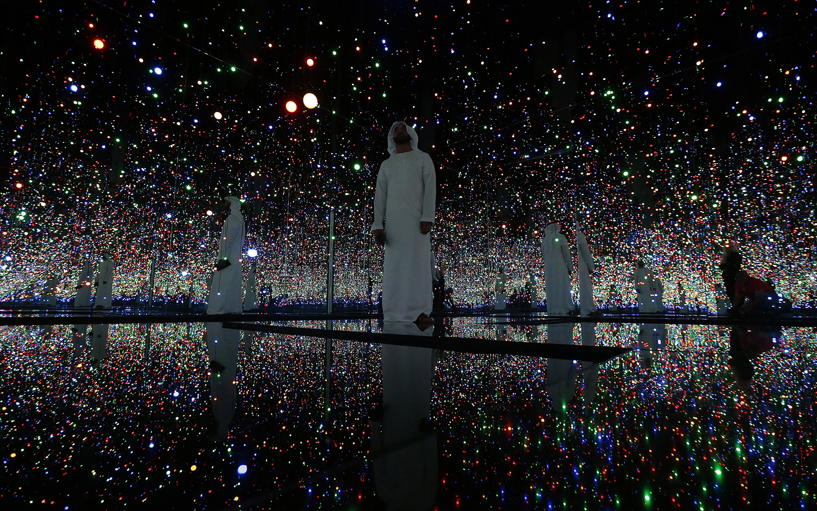 "TO GO WITH AFP STORY BY WISSAM KEYROUZVisitors walk inside an art installation by Yayoi Kusama titled ""Infinity Mirrored Room - Filled with the Brilliance of Life"" at a pre-opening exhibition titled ""Seeing Through Light Selection from the Guggenheim Abu"