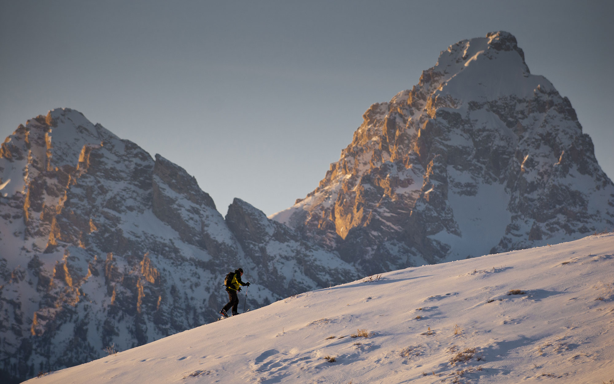 A young man climbs a hillside while backcountry skiing in Grand Teton National Park, Jackson Hole, Wyoming.