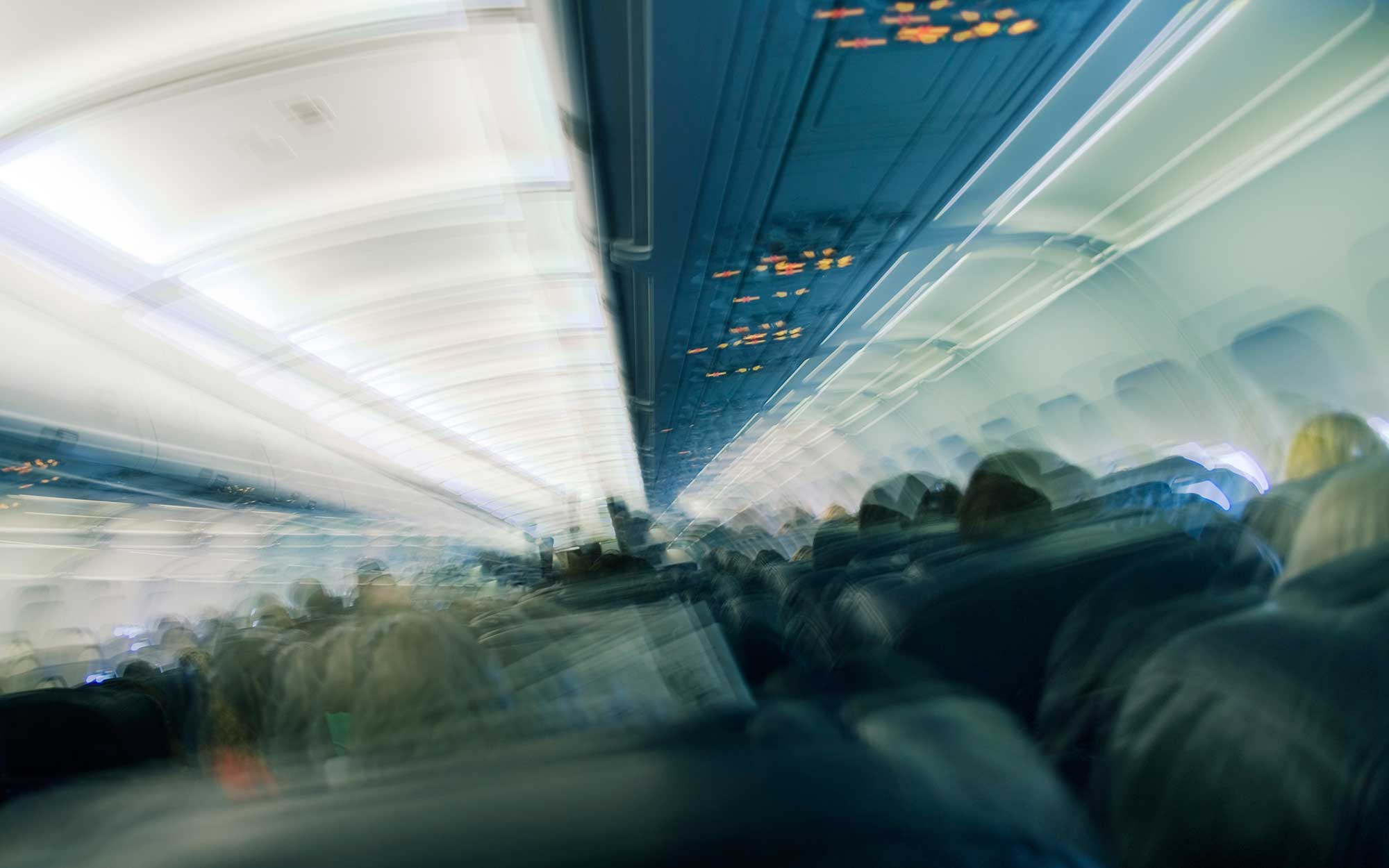 Seated passengers in aeroplane cabin, rear view (multiple exposure)