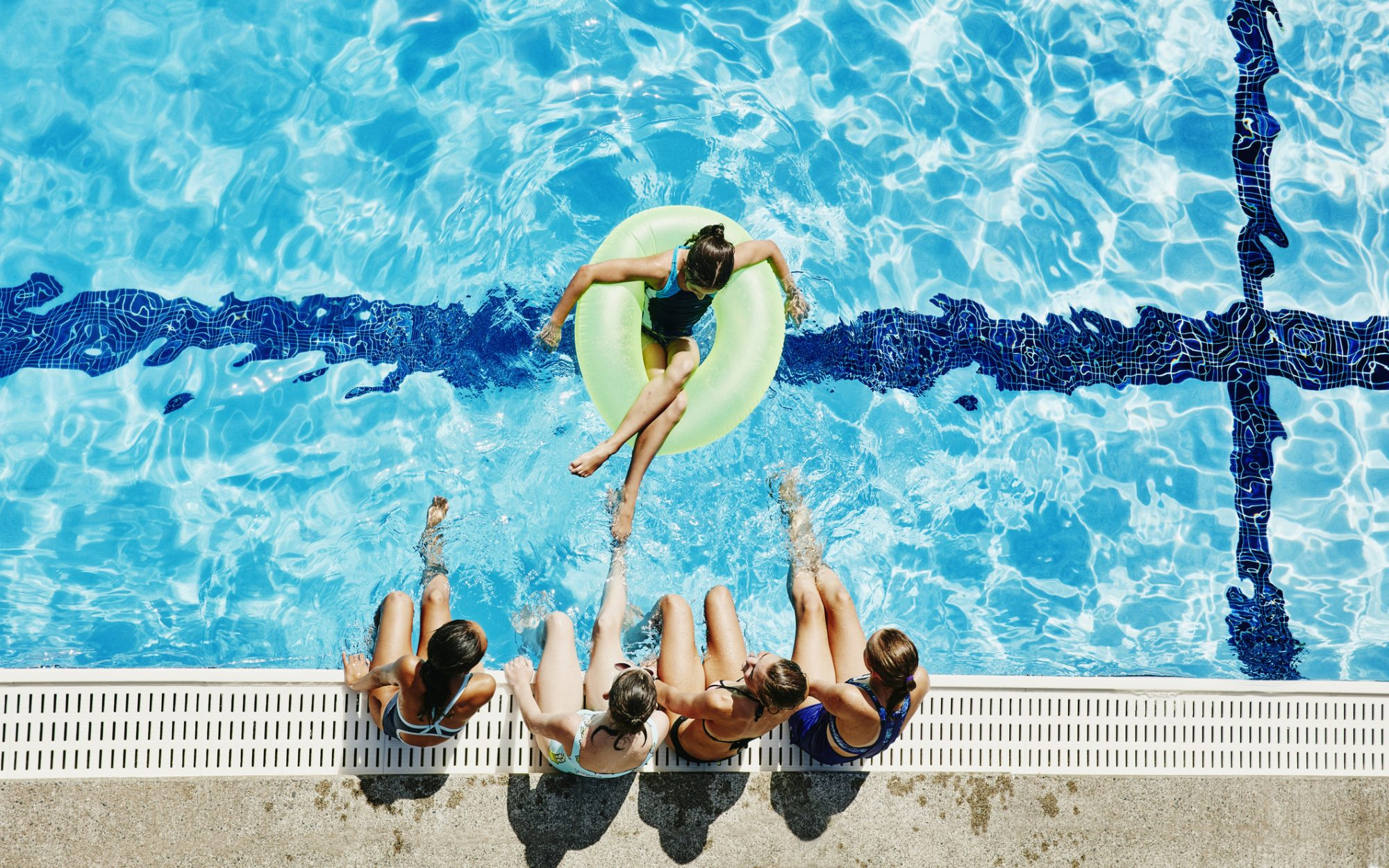 Overhead view of girls hanging out together at outdoor pool