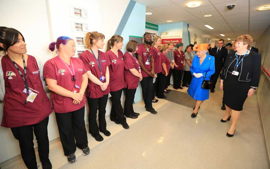 MANCHESTER, ENGLAND - MAY 25: Escorted by Kathy Cowell (right) Chairman of the Central Manchester University Hospital, Queen Elizabeth II greets staff during a visit to the Royal Manchester Children's Hospital on May 25, 2017