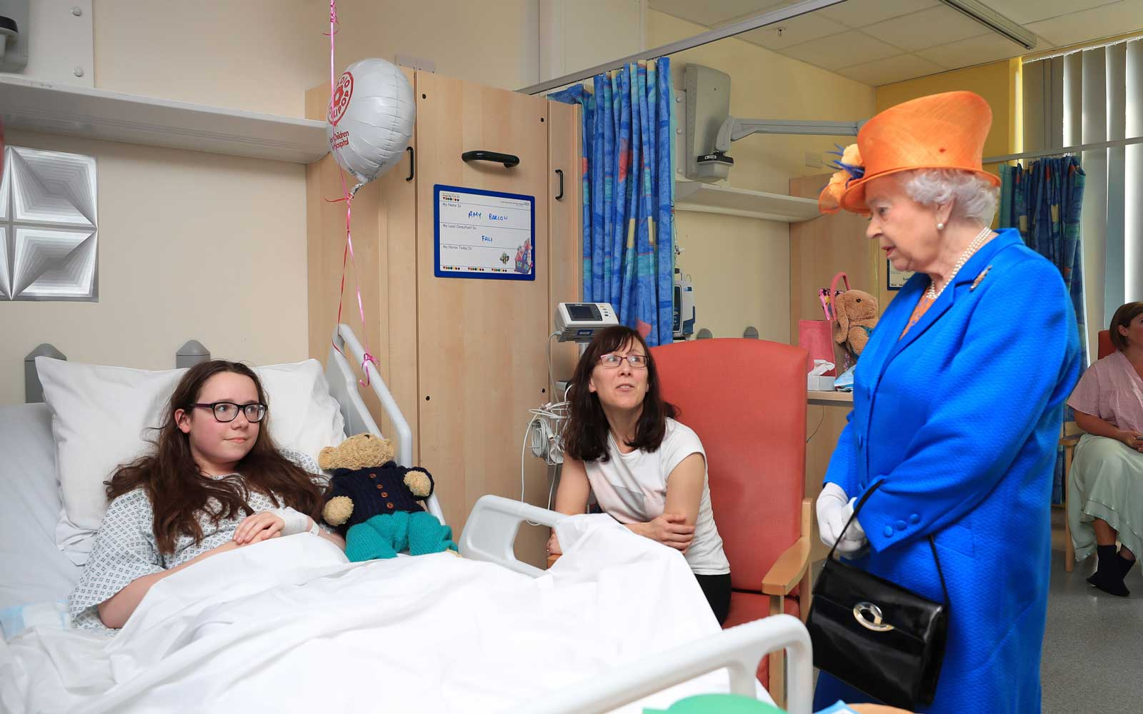 MANCHESTER, ENGLAND - MAY 25: Queen Elizabeth II speaks to Amy Barlow, 12, from Rawtenstall, Lancashire, and her mother, Kathy during a visit to the Royal Manchester Children's Hospital to meet victims of the terror attack on May 25, 2017