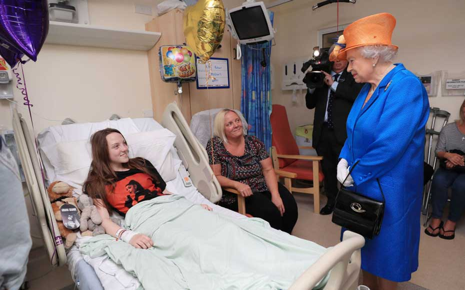 Queen Elizabeth II speaks to Millie Robson, 15, from Co Durham, and her mother, Marie, during a visit to the Royal Manchester Children's Hospital to meet victims of the terror attack on May 25, 2017