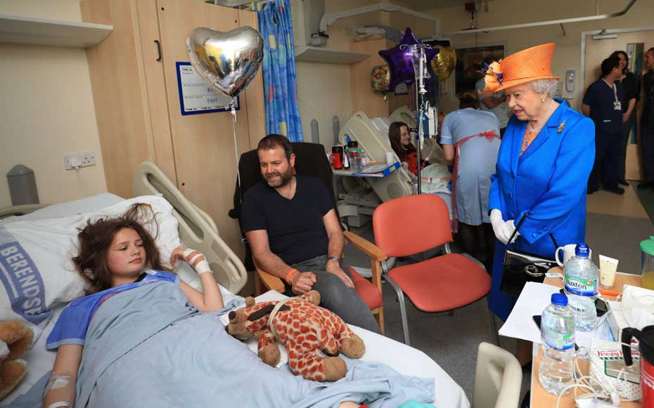 MANCHESTER, ENGLAND - MAY 25:  Queen Elizabeth II speaks to Evie Mills, 14, from Harrogate, her  mother, Karen and dad, Craig, during a visit to the Royal Manchester Children's Hospital to meet victims of the terror attac on May 25, 2017