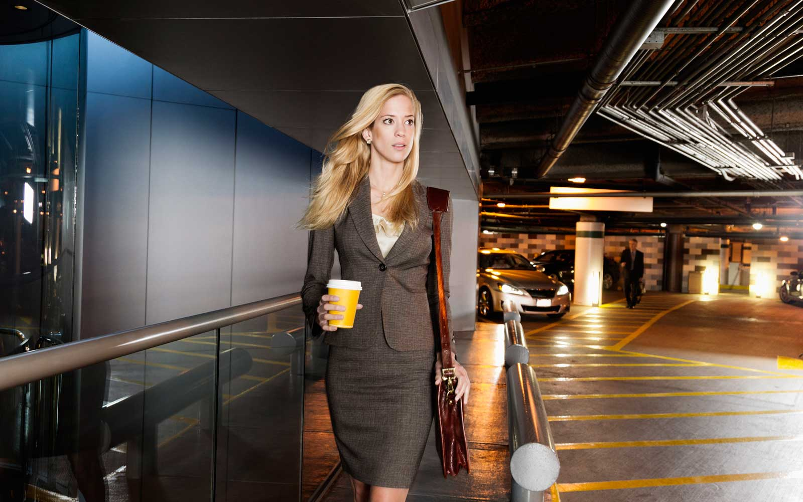 Businesswoman holding coffee and wearing a leather briefcase over her shoulder walking in a parking garage