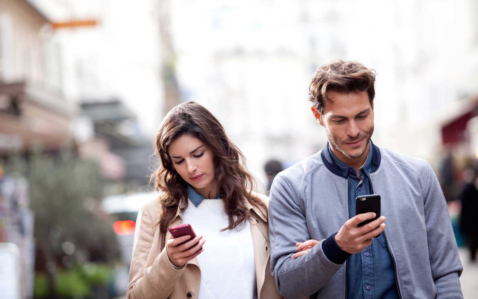 couple walking in the street watching their smartphone