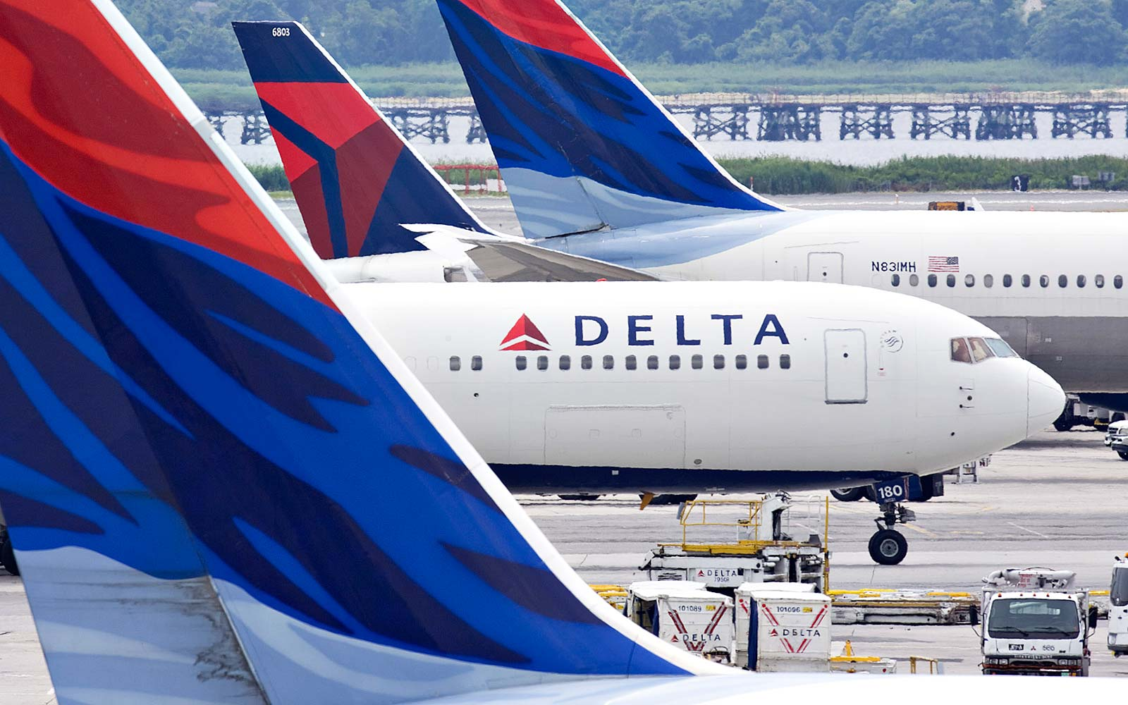 A Delta Air Lines plane taxis toward a gate between other Delta planes
