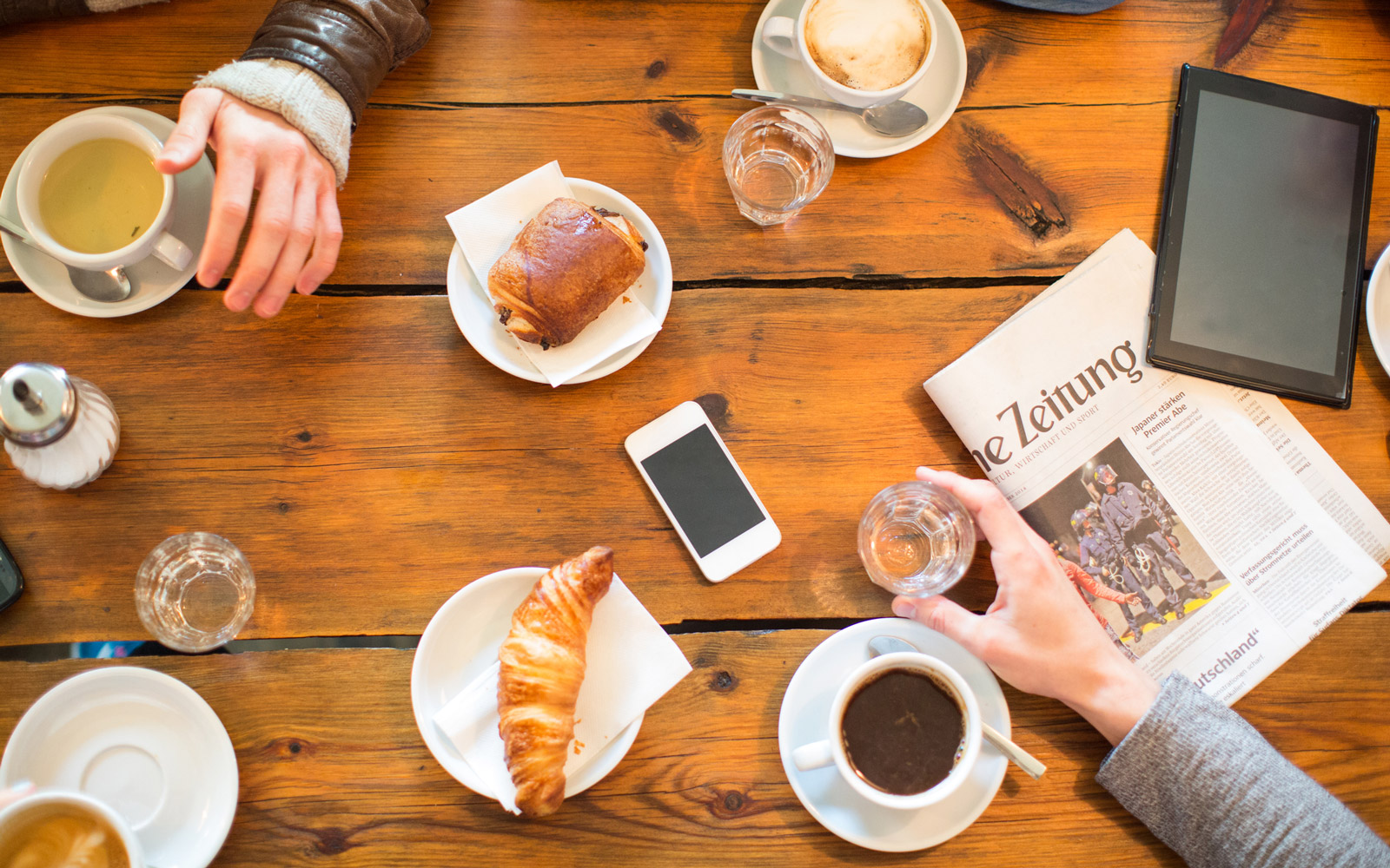 Cropped image of friends having coffee and snacks at table