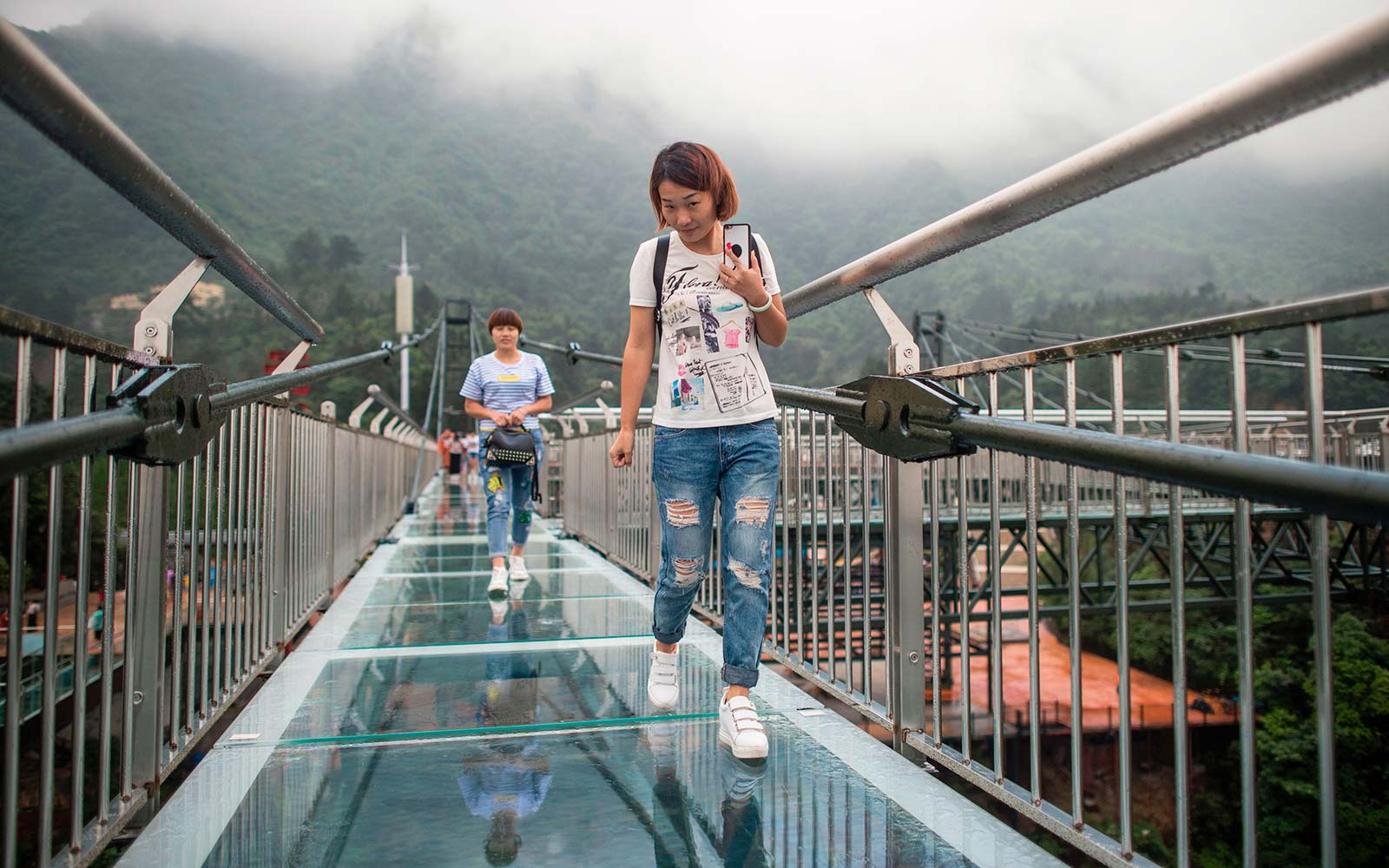 Tourists look on from a glass-bottomed skywalk.