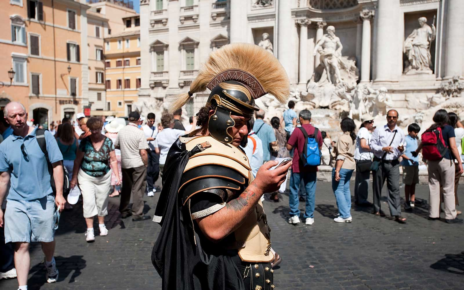 A man dressed up like an ancient Roman, in front of the Trevi fountain, is checking his mobile phone, w