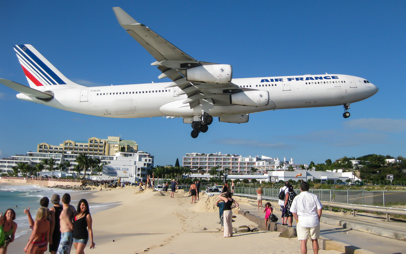 A plane lands at Maho Beach.