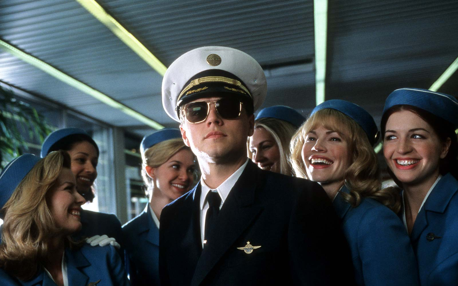 Leonardo DiCaprio with airline stewardess surrounding him in a scene from the film 'Catch Me If You Can' travel pilot