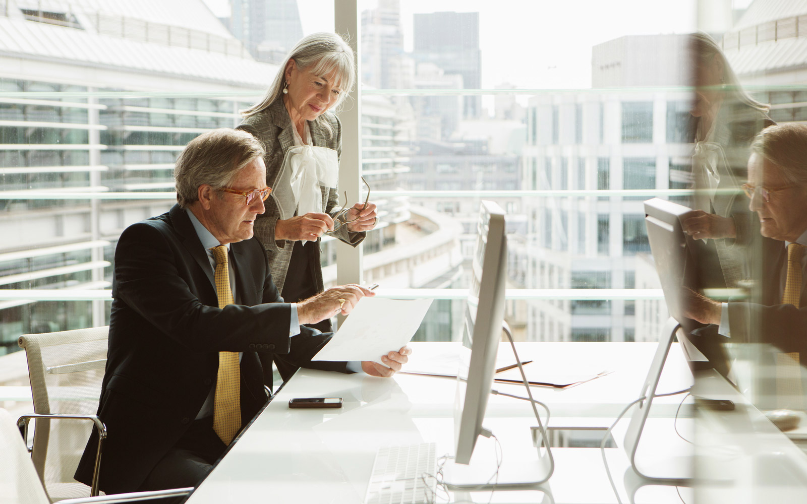 Older businessman and businesswoman working in an office