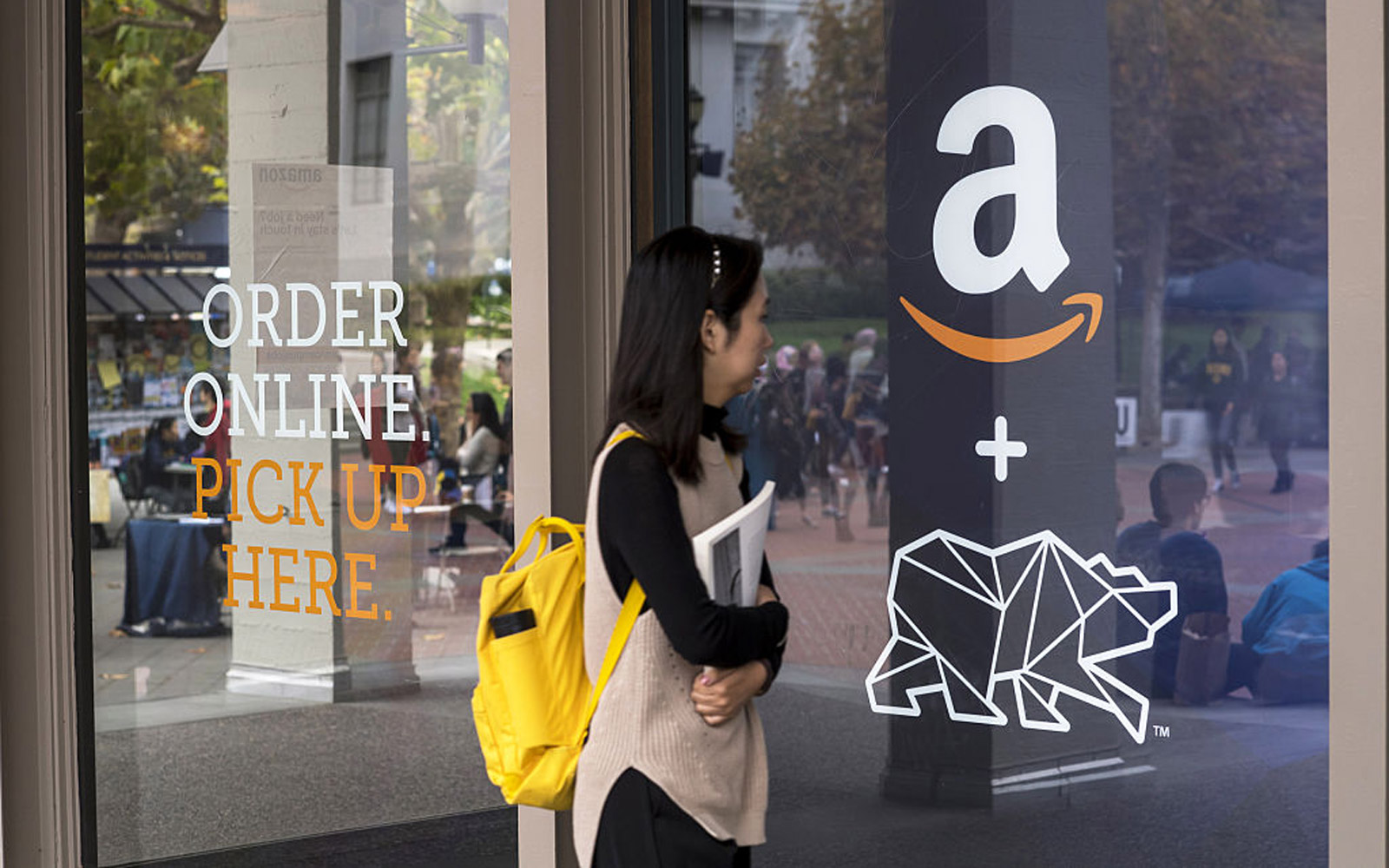 A student walks in front of an Amazon.com Inc. kiosk on the University of California, Berkeley campus in Berkeley, California, U.S., on Wednesday, Oct. 12, 2016. By the end of the year, Amazon will have staffed pickup kiosks serving more than 500,000 coll
