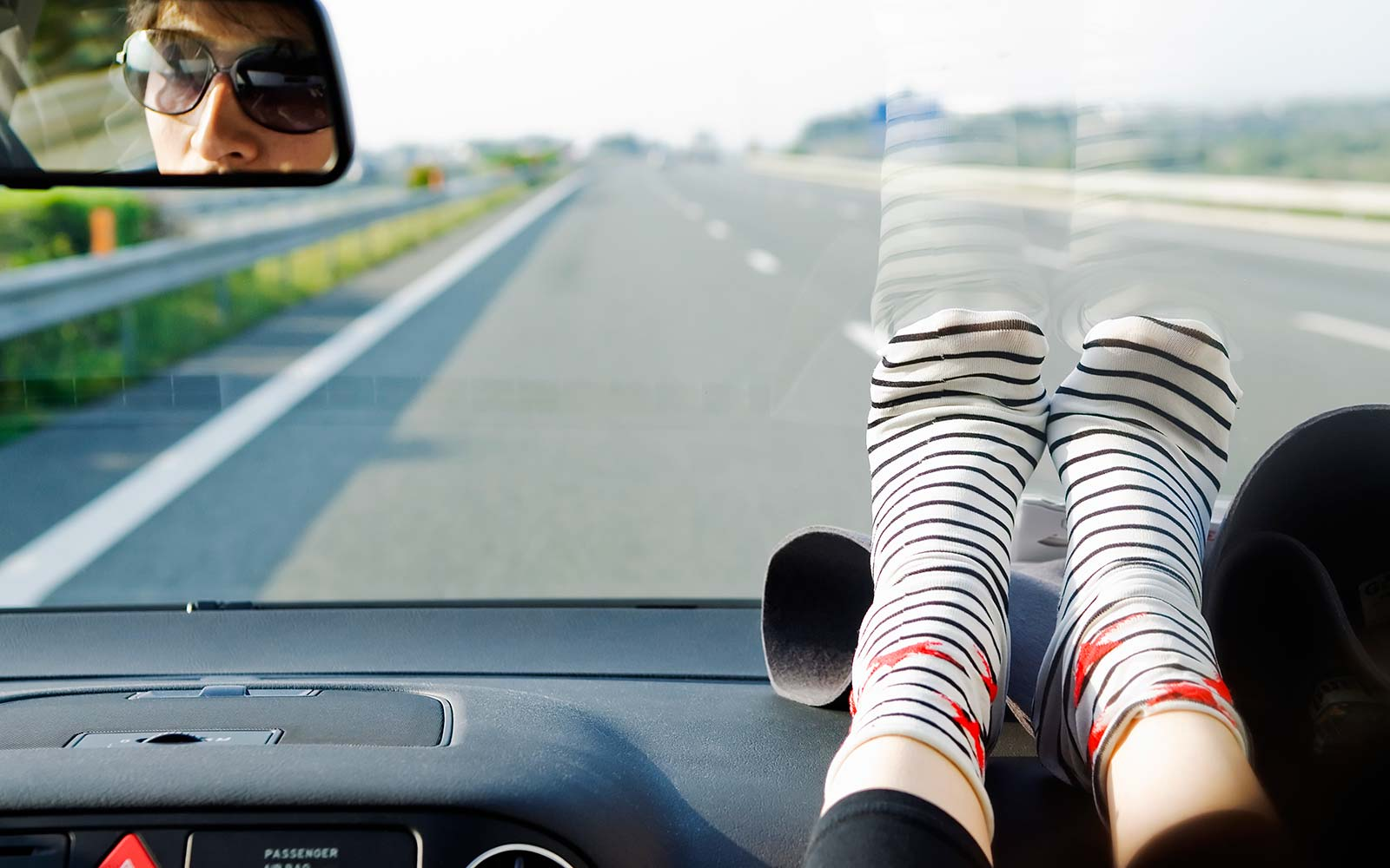 Driving road trip feet on dashboard drive danger warning