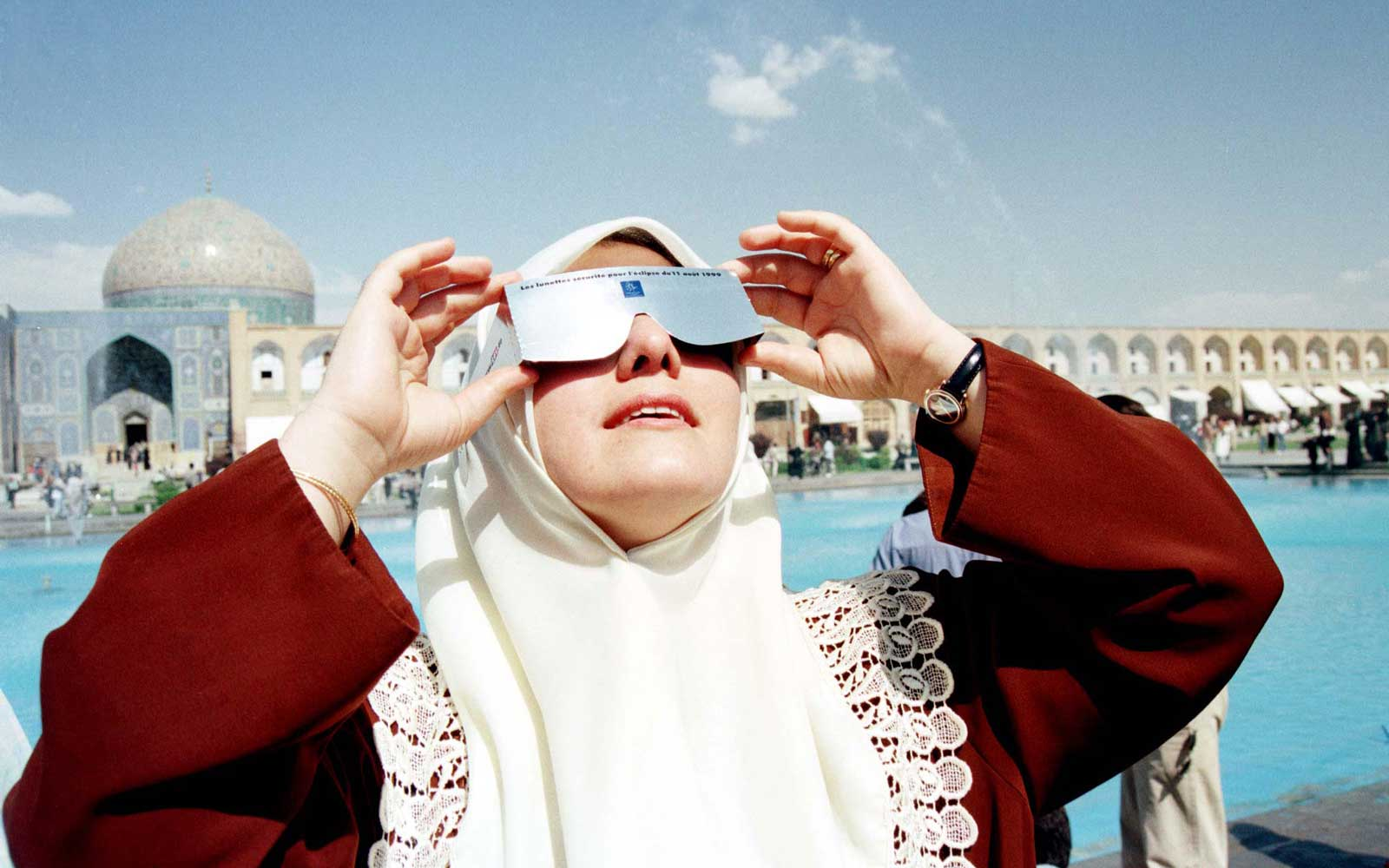 A woman viewing a total solar eclipse through filtered glasses in Naqsh-e Jahan Square, Isfahan, Iran