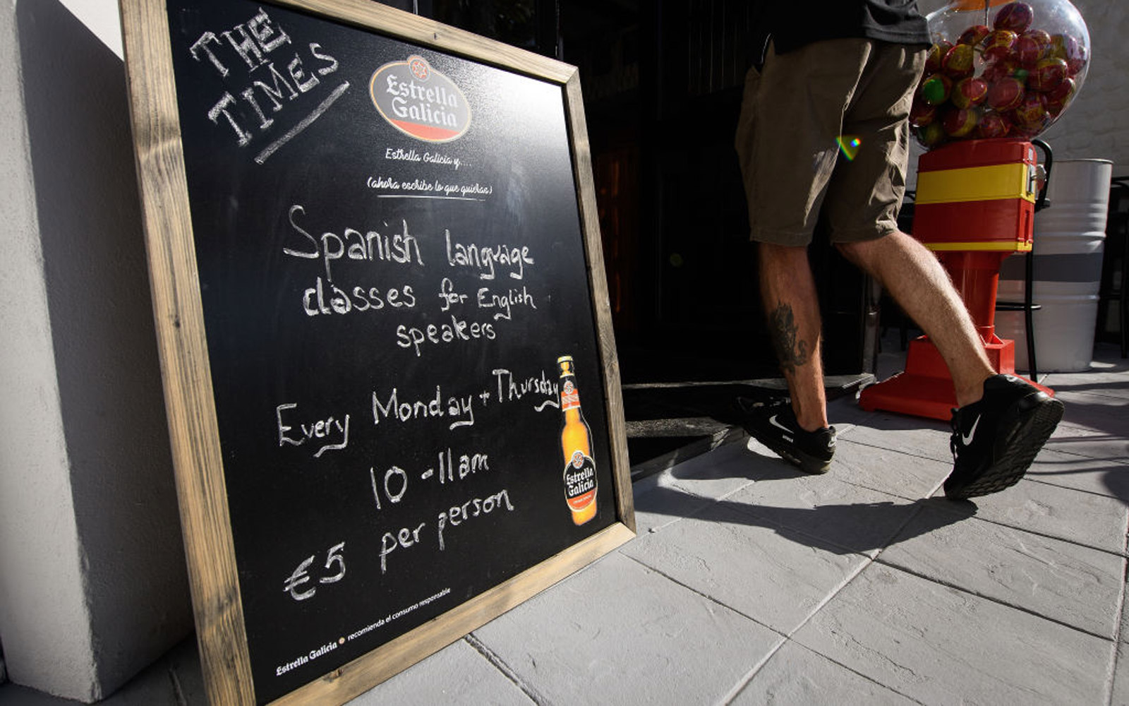 """MIJAS, SPAIN - JULY 23:  A man passes a sign advertising discount Spanish lessons for British customers at the British bar """"The Times"""" on July 24, 2017 in Mijas, Spain.  With Brexit discussions yet to provide answers to a number of questions relating to t"""