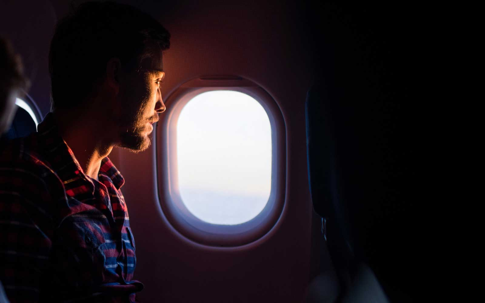 Young man sitting in an airplane and looking through window.