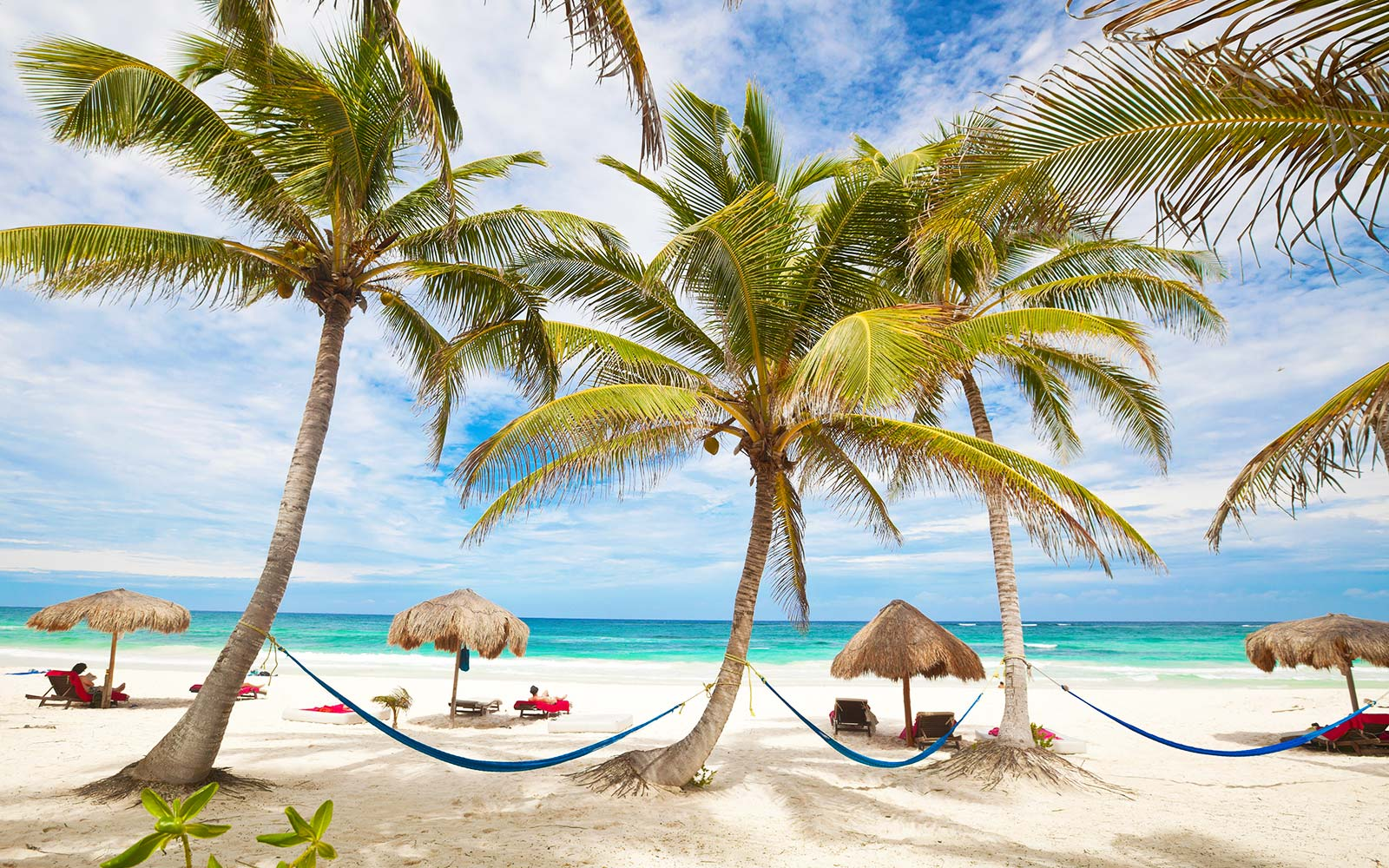 Tropical beach vacation destination with hammocks, beach chairs, and palm trees in Tulum, Mexico Cara Delevingne Birthday