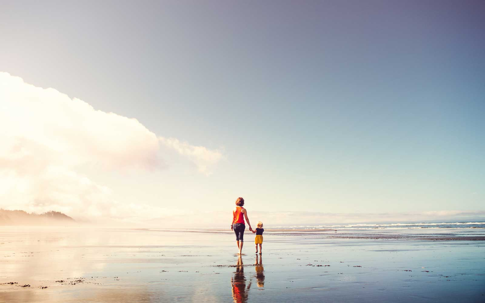 A young woman and a little girl walk on a beautiful sunny Washington state beach