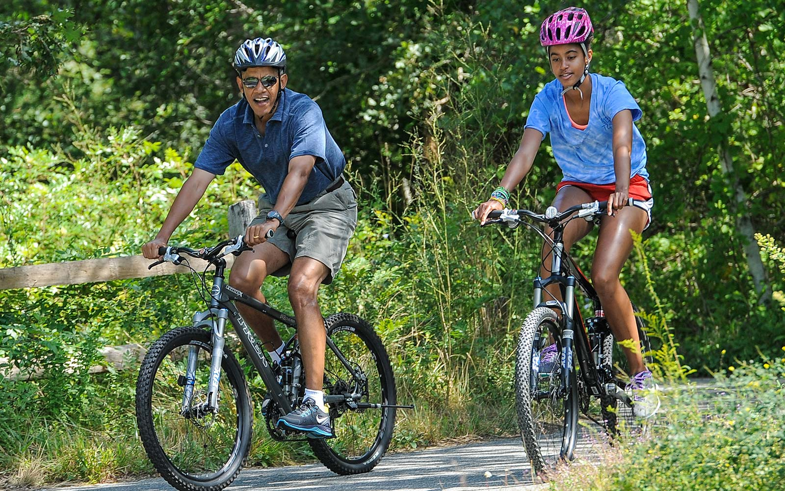 Barack Obama and his daughter Malia Obama ride a bike during a vacation on Martha's Vineyard in West Tisbury, Massachusetts. Obama and his family are on a weeklong vacation