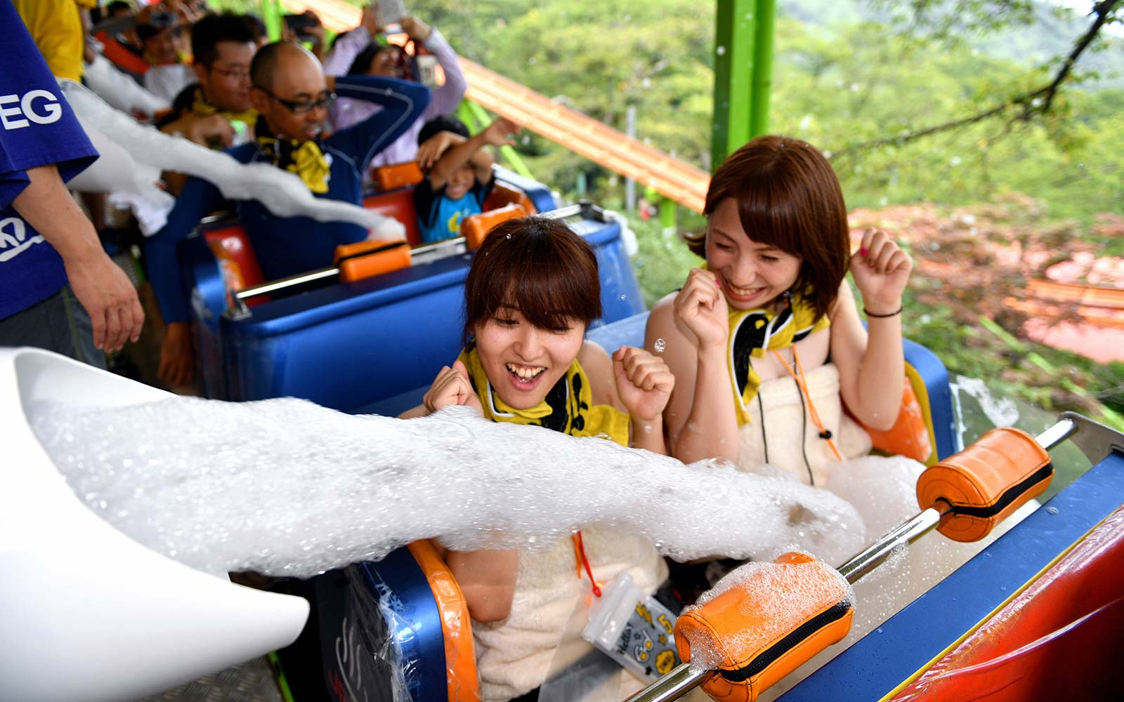 """Visitors are splashed foam while riding a rollercoaster in """"Yu-enchi"""" Spamusement park in Beppu, Oita, Japan Rakutenchi Hot Spring Onsen Theme Park"""