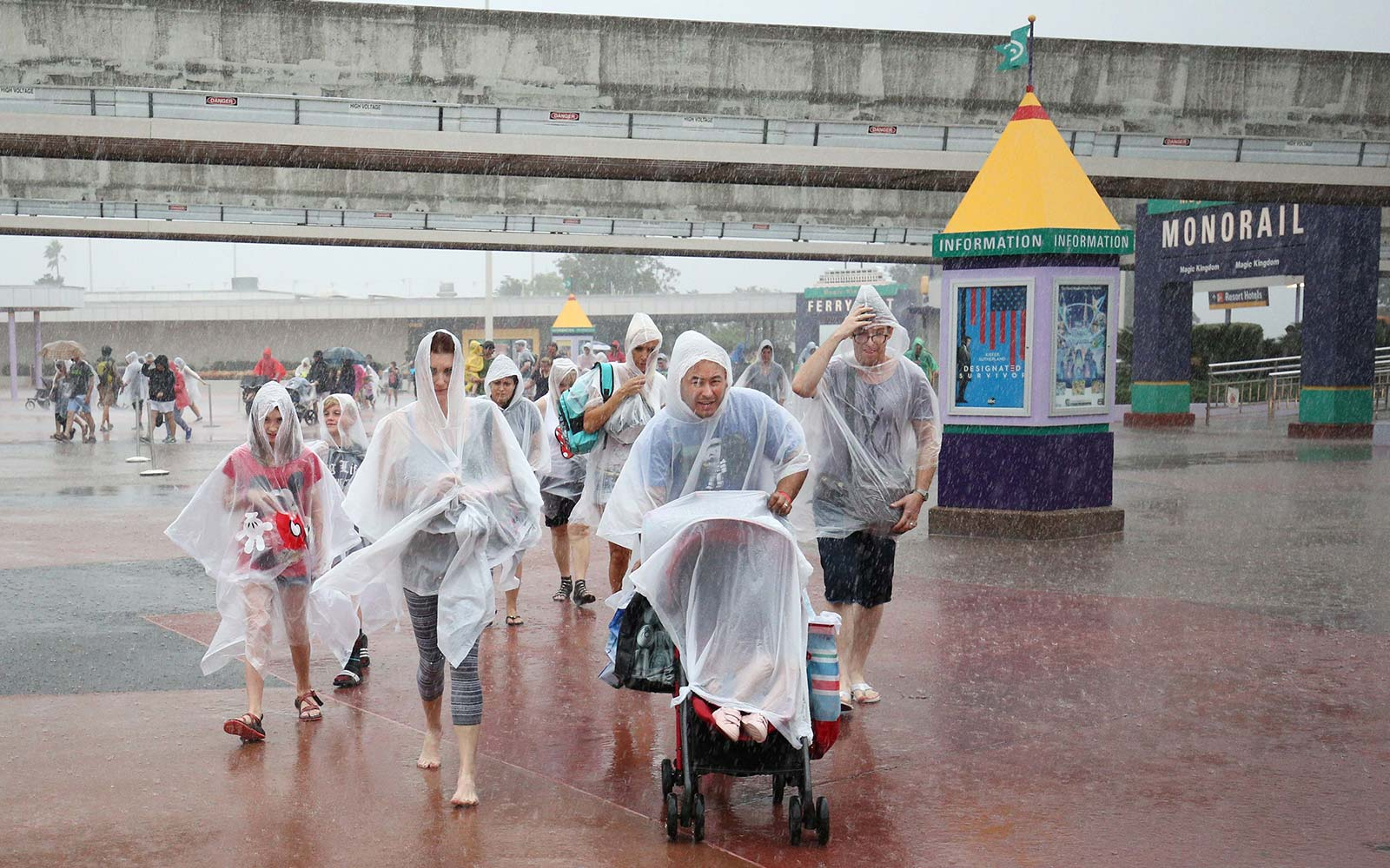 People leave Disney's Magic Kingdom theme park, in heavy rain, after it closed in Orlando, Florida in preparation for the landfall of Hurricane Matthew, on October 6, 2016. Some three million people on the US southeast coast faced an urgent evacuation or