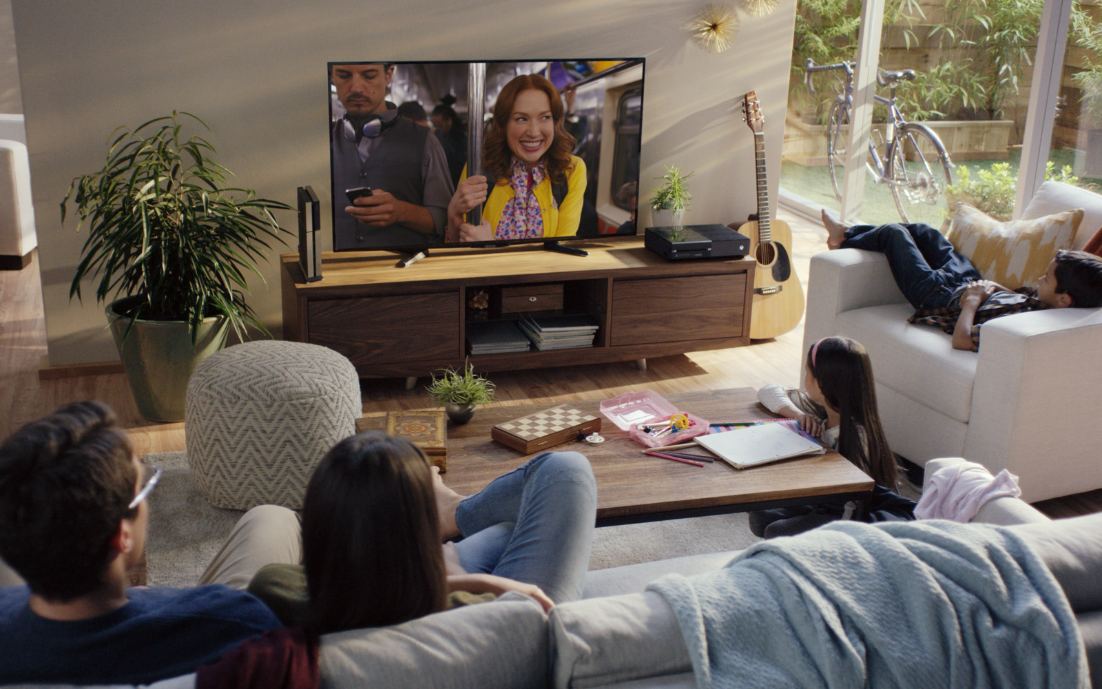 Family of four watching Unbreakable Kimmy Schmidt in their family room