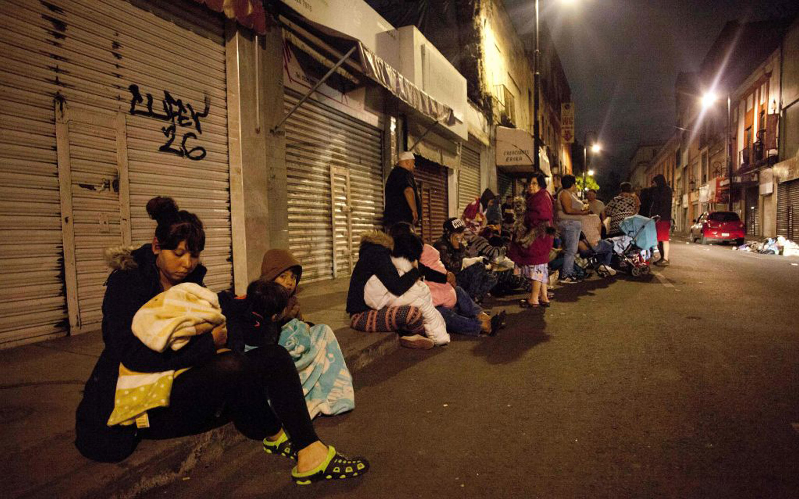 People sitting on the sidewalk after the earthquake in Southern Mexico