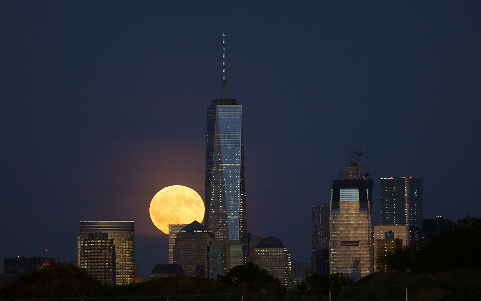 A full harvest moon rises behind Lower Manhattan and One World Trade Center in New York City