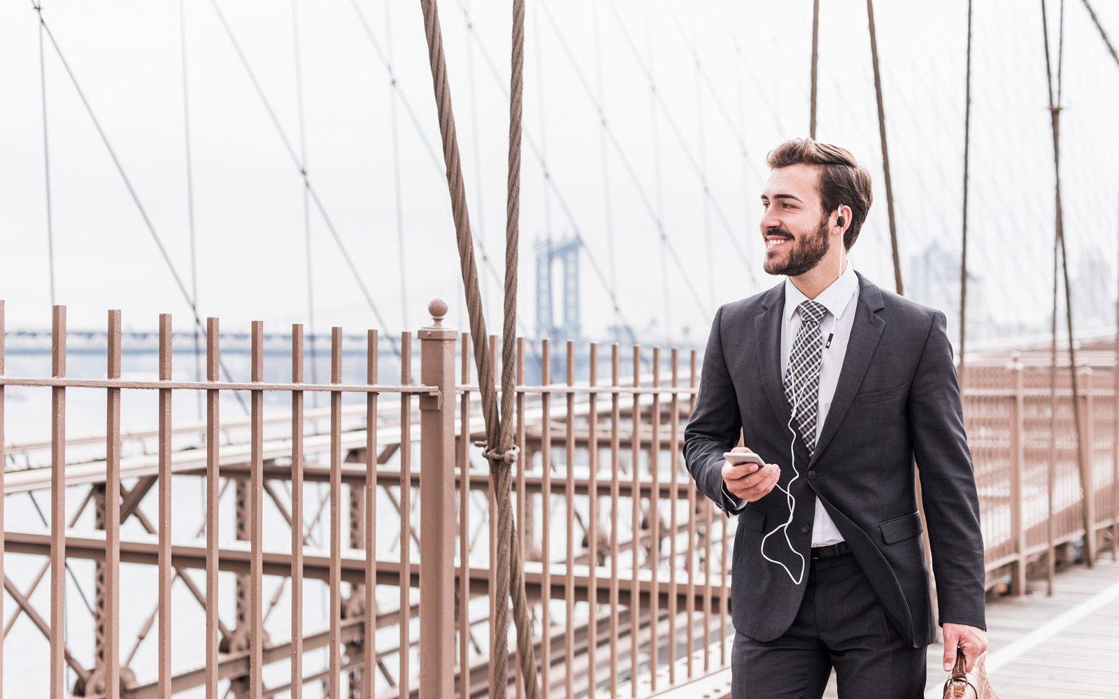 USA, New York City, smiling businessman with cell phone and earbuds on Brooklyn Bridge