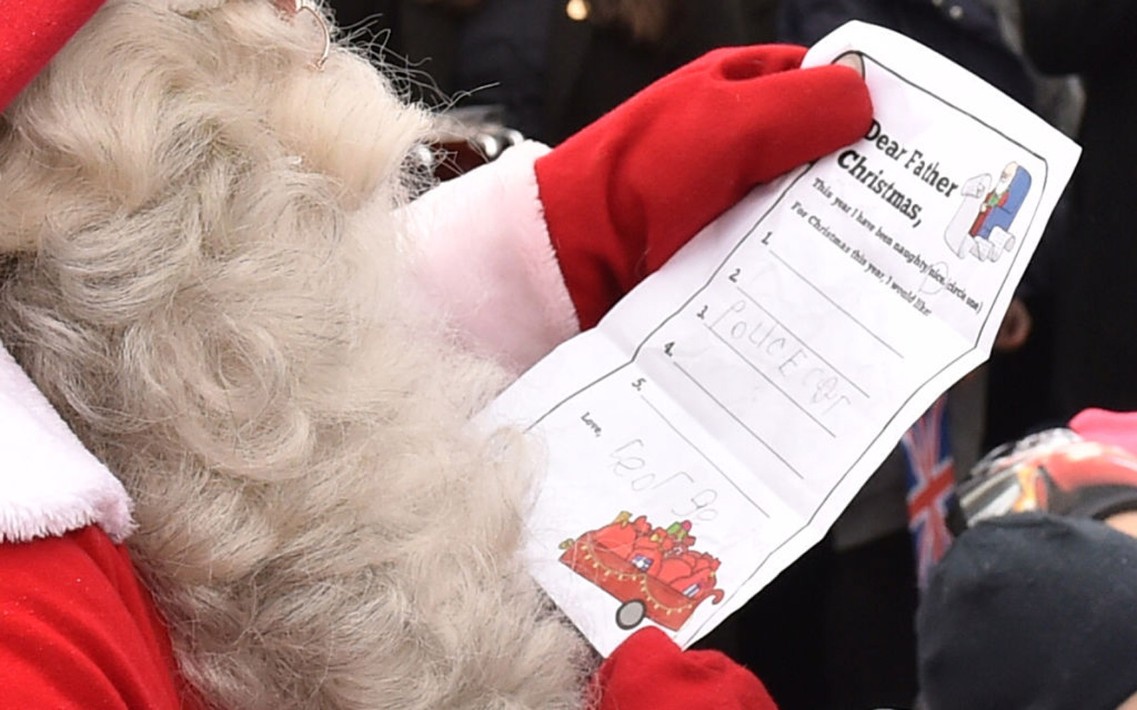 The Duke of Cambridge hands Prince George's Christmas Wish List to a man dressed as Santa Claus as he visits Esplanade Park's Christmas market in Helsinki