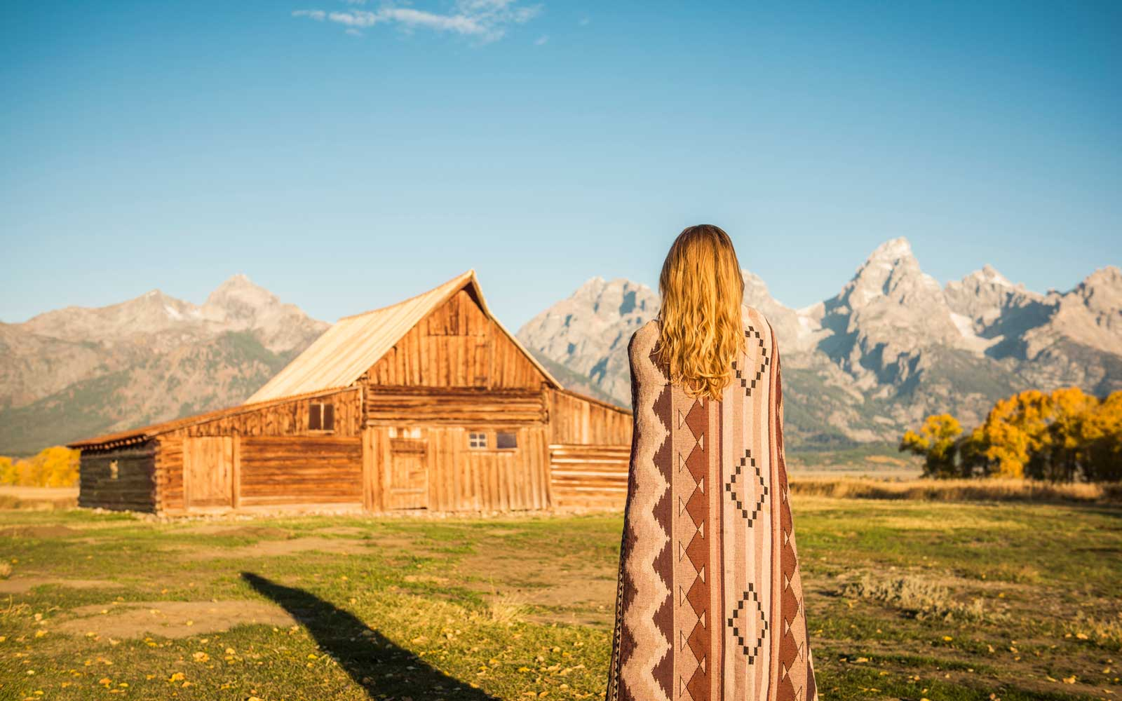Woman standing in front of barn in a mountainous landscape
