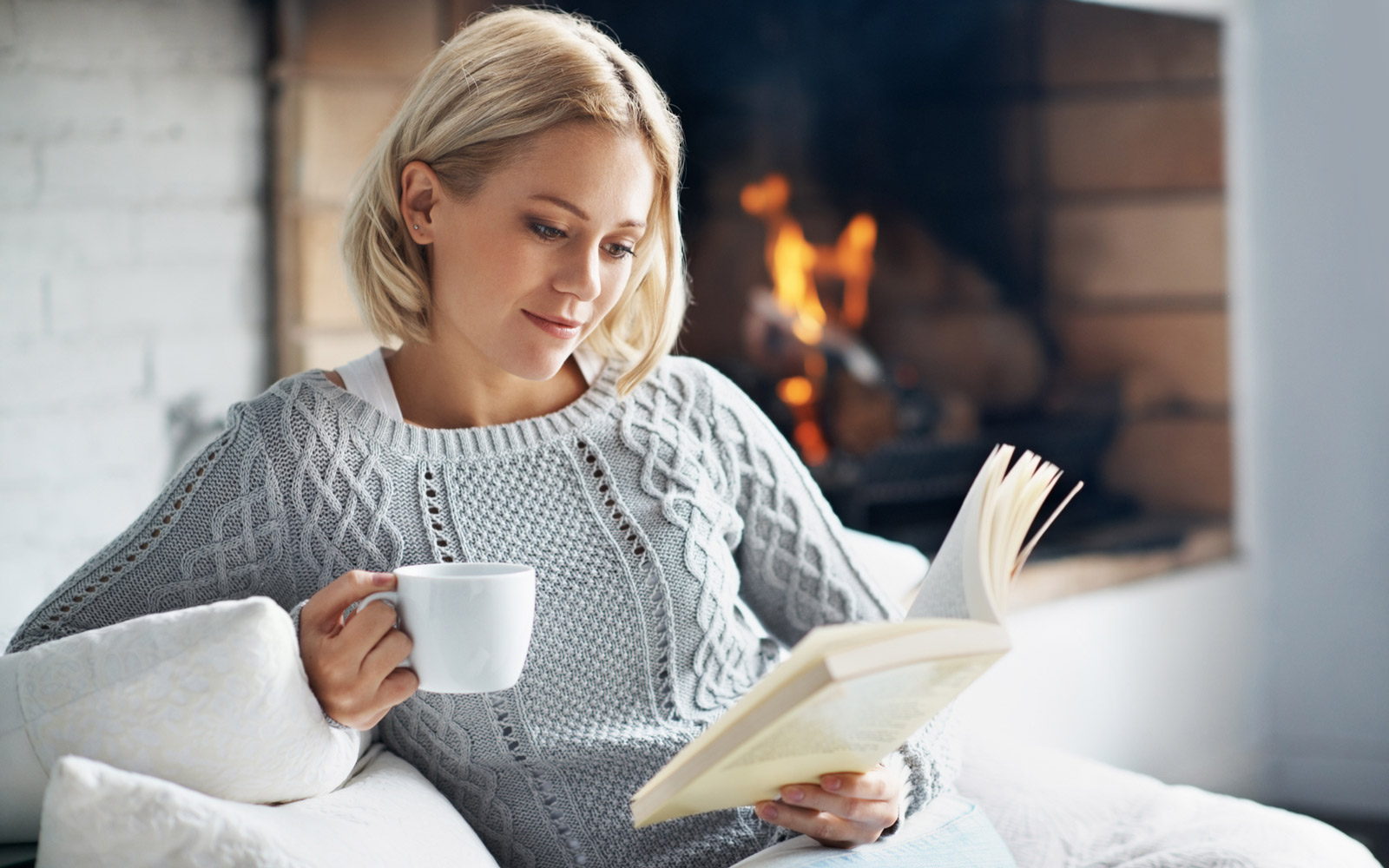 A beautiful young woman reading a book and enjoying a warm beverage near a fireplace
