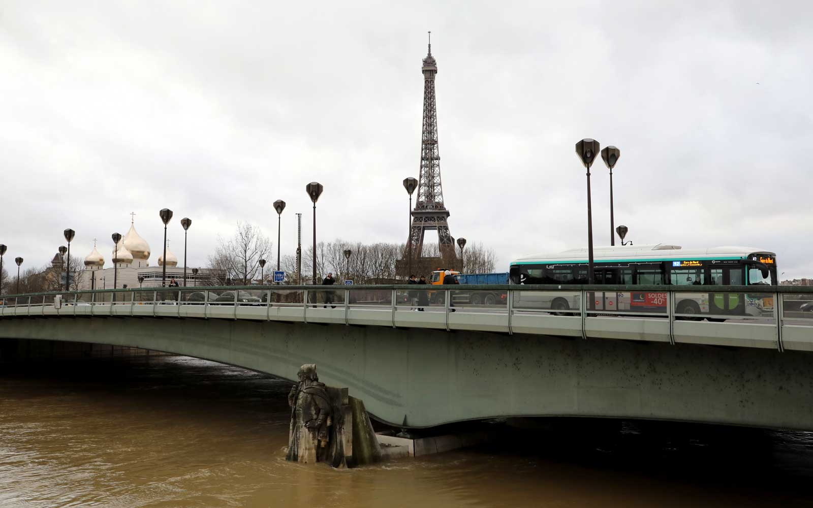 Traffic moves across the Pont D'Alma bridge past the Eiffel Tower and the Holy Trinity Cathedral, as the Zouave statue stands partially submerged   after the River Seine burst its banks in Paris on January 24, 2018.