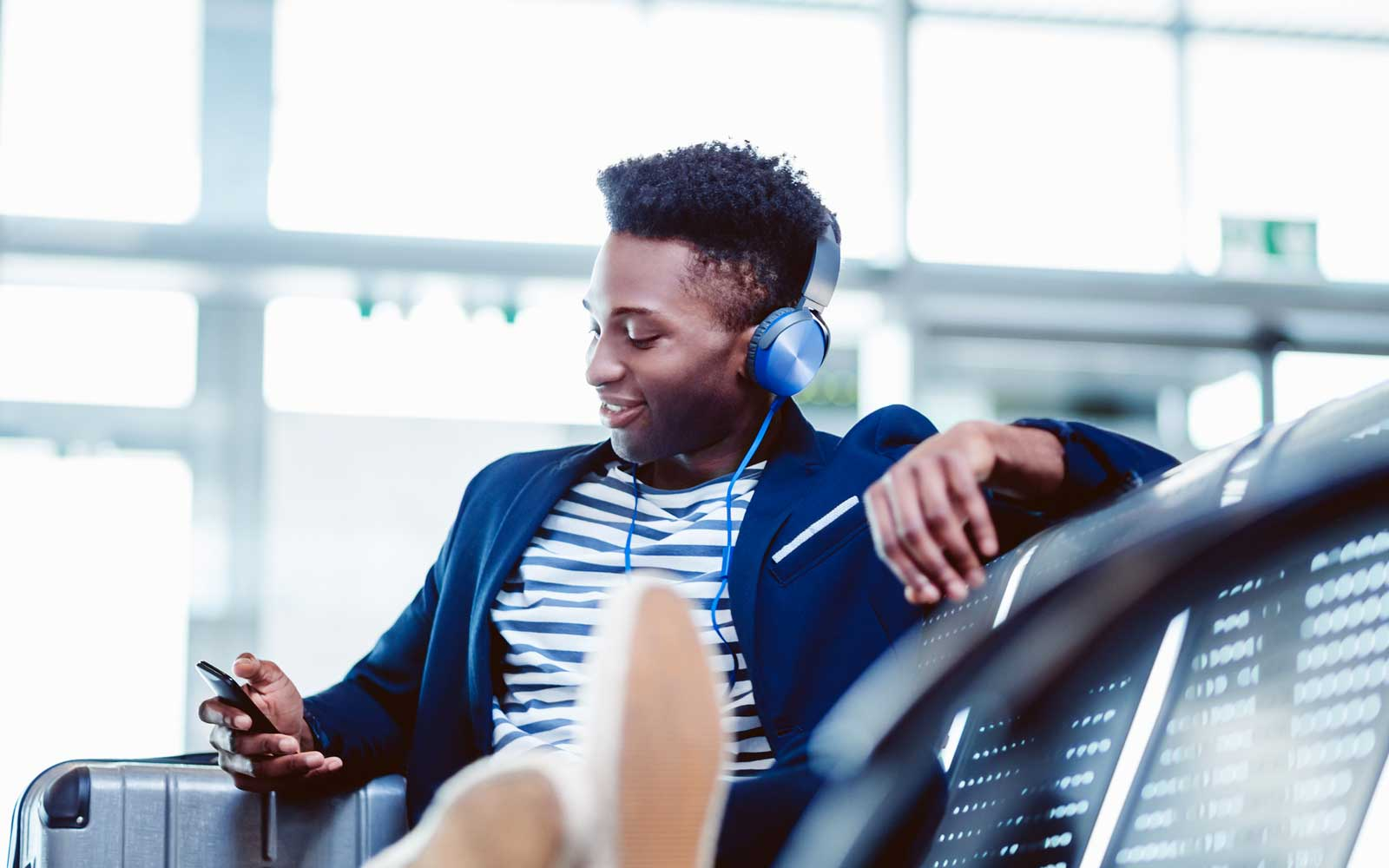 A young man uses his phone while waiting at an airport