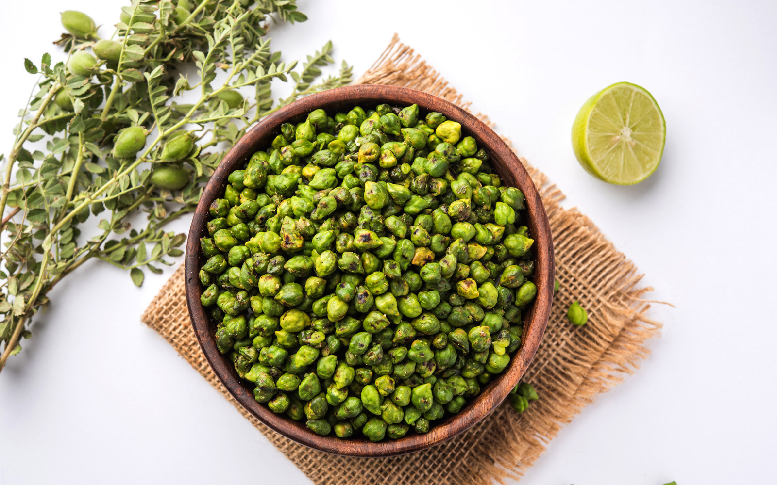 Roasted fresh Green Chickpeas or Chick Peas or harbara in hindi also known as Cicer with pinch of salt and chat masala and lemon, popular snack from India/asia